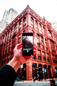 A woman's hand taking a photograph of a building using her cell phone