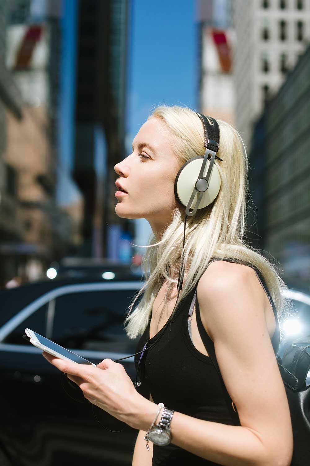 Woman walking down the city streets listening to music on her smartphone via headphones
