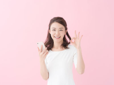 A girl on her smartphone, gesturing with an 'OK' sign directly to the camera