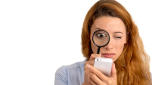 A woman looking at her smartphone through magnifying glass
