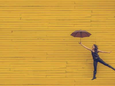 Woman holding an umbrella against a yellow brick wall