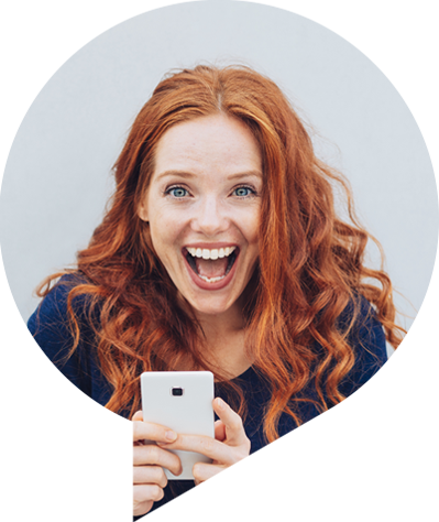Red headed woman holding a phone and smiling