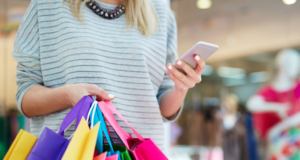 Woman holding mobile phone and shopping bags